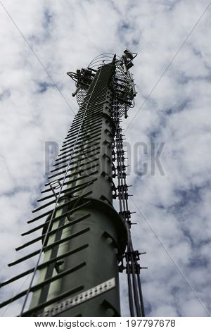 antenna supporting tower with white cloudy sky