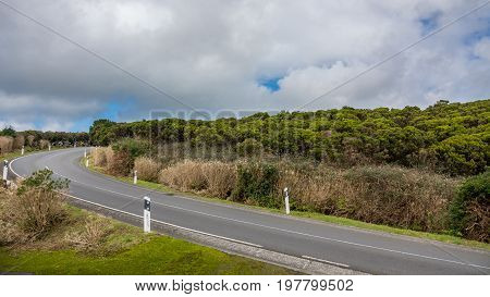 Cloudy sky and road curve through volcanic terrain