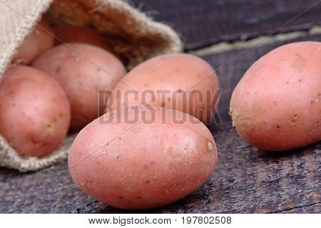 Red potatoes in a jute sack on wooden table