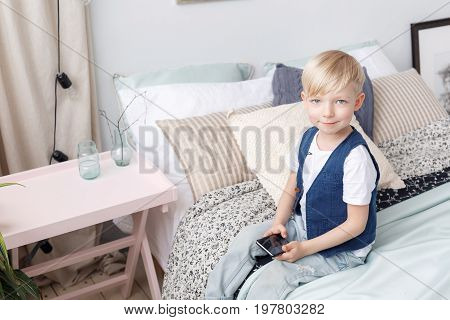 Smart small boy with mobile phone, seats on bed in bedroom. Technology concept.