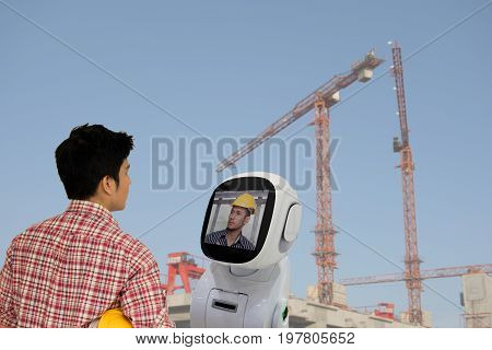 engineer use robot advisor technology to talk with boss or team mate for consult at construction site to improve a work a futuristic robot help a work to easy