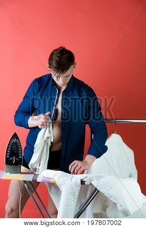 Man ironing clothes with iron on board. Macho in open blue shirt on red background. Ironed shirts hanging on rack. Housework and housekeeping concept poster