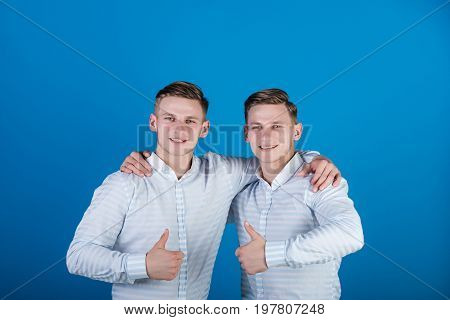 Happy men hugging and showing thumbs up gestures. Twins wearing striped shirts. Models standing together. Family brotherhood and friendship concept. Two brothers smiling on blue background.
