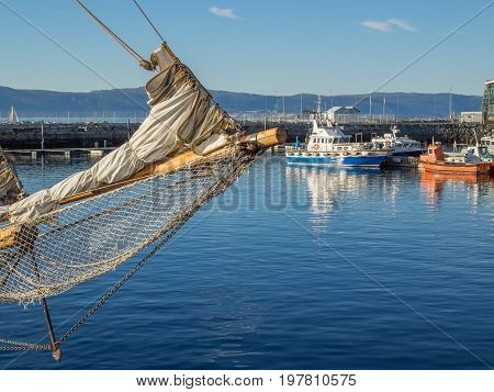 The Brattor Quay in downtown Trondheim Norway with the bowsprit of a sailing ship in the foreground and a pilot boat and other utility vessels out if focus in the background.