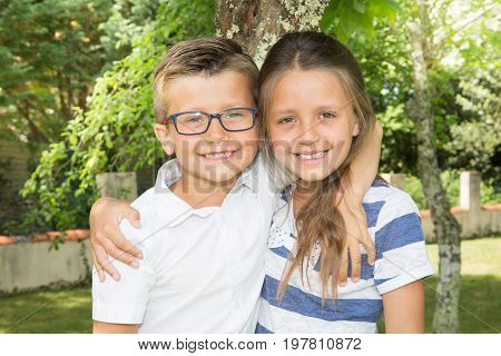 Portrait Of Adorable Brother And Sister Smile And Laugh Together While Sitting Outdoors. Happy Lifes