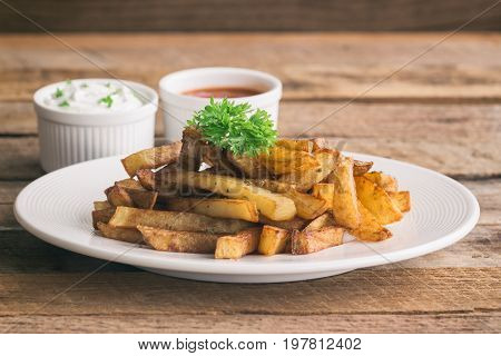 Homemade french fries serve with ketchup and sour cream or mayonnaise.Golden brown crispy french fries sprinkle with salt and oregano on white plate for snack or appetizer.French fries on wood table.Delicious french fries with dipping sauce