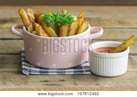 Homemade french fries serve with ketchup and sour cream or mayonnaise. Golden brown crispy french fries sprinkle with salt and oregano on bowl for snack or appetizer. French fries on wood table. Delicious french fries with dipping sauce.