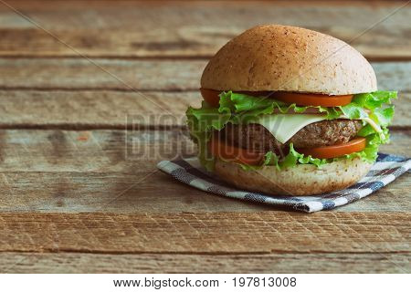 Homemade hamburger on wood table. Delicious sandwich hamburger with meat or pork ham cheese and fresh vegetable. Hamburger or sandwich is the popular fast food for brunch or lunch.Cheese burger ready to served on wood table with copy space.