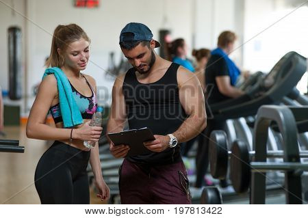 Young woman working with personal trainer in gym. Male coach and female client discussing training plan. Healthy lifestyle, fitness and sports concept.