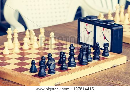 Chess Board With Chess Pieces And Chess Clock On Wooden Desk In Connection With The Chess Tournament