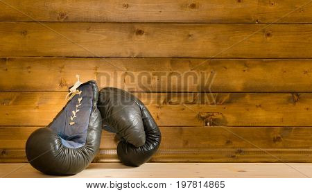 Gloves for boxing on the floor against the background of a wooden wall