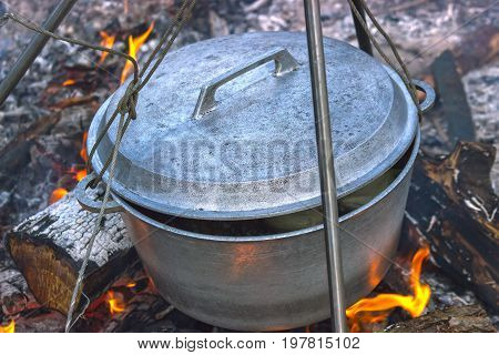 Cooking in sooty cauldron on campfire at forest poster