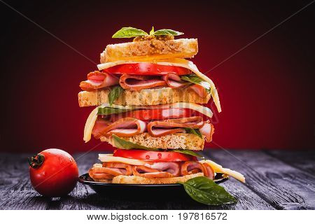 Club sandwich with cheese, basil, tomato, ham on the black wooden table