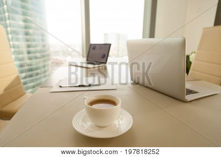 Modern office workplace with conference negotiating table and two laptops, focus on cup of coffee, break during work, preparation to formal meeting in boardroom, executive management working space