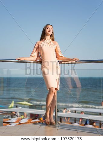 A cute romantic female wearing a light pink dress. A tall glamorous young lady relaxing on a sunny glass terrace on a saturated blue sea background. Elegance, beauty, fashion concept.