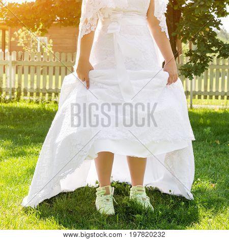 Funny beautiful bride wearing green running shoes. Runaway Bride, close up