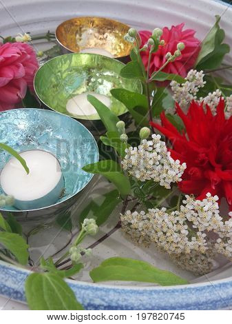 beautiful decoration with multi colored blossoms and tea lights in glossy trays