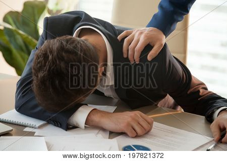 Tired businessman falls asleep at workplace, lying on office desk with papers, feeling stressed depressed because of hard work failure, wants to quit, giving up, male hand waking him up or supporting poster