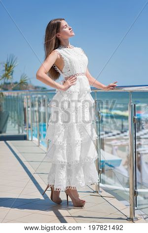 A gorgeous, confident female is posing on a sunny transparent balcony on a blue sky background. The stylish woman with light brown hair in a long dress. The amazing girl on a summer vacation.