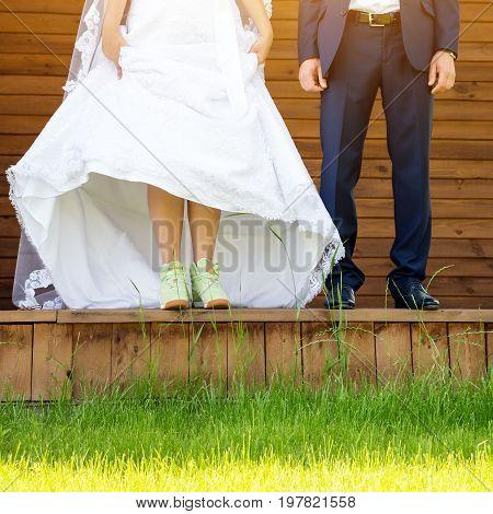 Funny beautiful wedding couple. Bride wearing green running shoes. Runaway Bride, close up