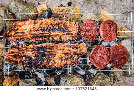 Pork Ribs And Burgers On Homemade Improvised Bbq Barbecue Grill.