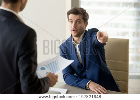 Furious boss firing incompetent employee, angry ceo dissatisfied with bad work result and declining project rates in financial report, telling to get out, dismissing subordinate for being ineffective