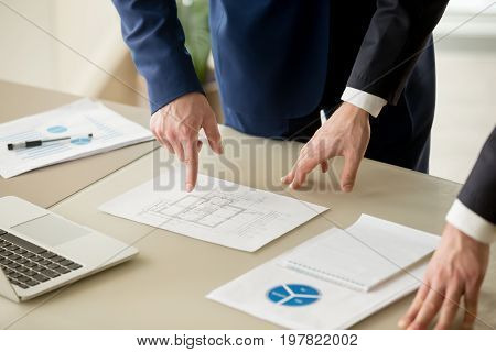 Close up view of businessmen discussing building plan, property value estimation, analyzing real estate market with infographic statistics, house evaluation, construction investment, home appraisal poster