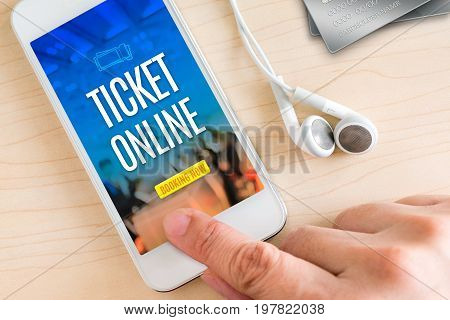 Hand touch smart phone and ear phone with Ticket online word on wood table Online payment concept