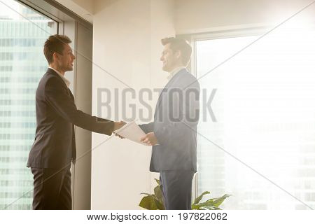 Two smiling businessmen shaking hands in sunny office, happy partners sealing deal, handshaking after signing papers, making agreement, concluding contract, finishing meeting with good impression