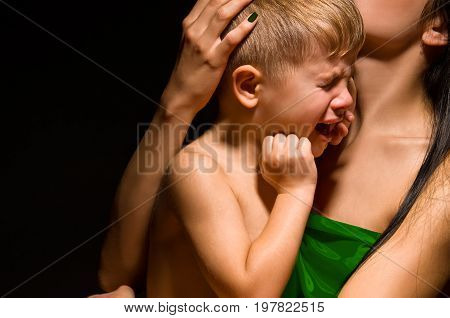 Portrait of a beautiful crying child on the mother's arms