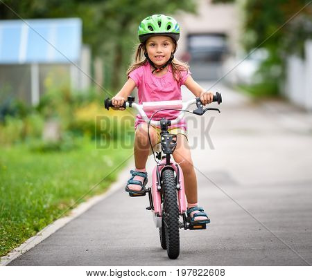 Children Learning To Drive A Bicycle On A Driveway Outside.