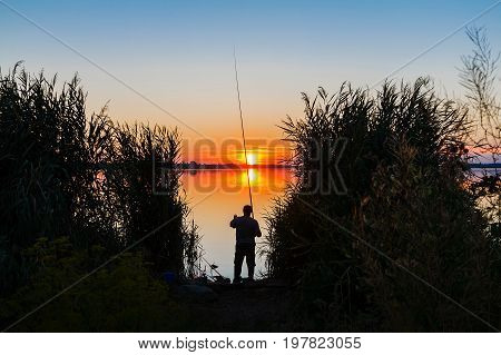 Sunset over the lake. On the shore is a fisherman and casts a fishing pole.