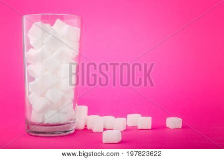 A glass of sugar crystals or cubes on a bright pink background. A few sugar cubes are near the full glass with white sugar. Intake of bad calories. Copy space.