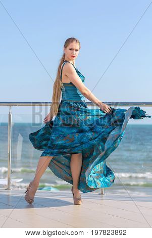 An attractive young female in a long silk emerald dress on a light blue sky background. The beautiful girl in a stylish dress on a glass balcony. A concept of femininity, peace, and harmony.