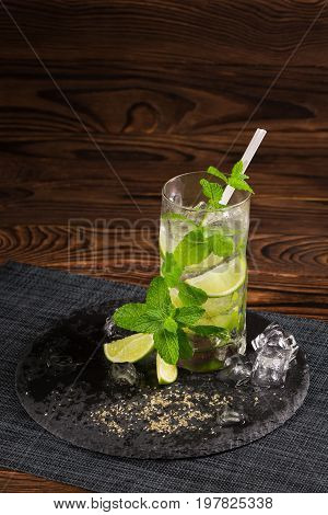 A beautiful green mojito cocktail with a white straw on a dark wooden background. An alcohol beverage with fresh lime slices, brown sugar, ice cubes and mint leaves. Alcoholic summer beverages.