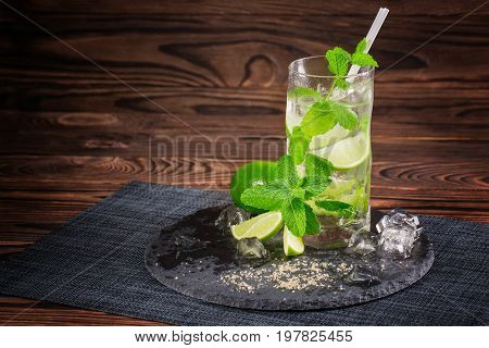 A beautiful and organic mojito on a dark wooden background. A glass of green mojito with slices of lime, mint, white straw, and ice cubes. A refreshing summer beverage on a black plate on a fabric.