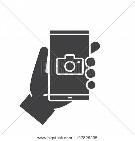 Hand holding smartphone glyph icon. Silhouette symbol. Smart phone photocamera. Negative space. Vector isolated illustration