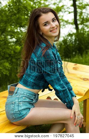 Cheerful young girl in blue t-shirt and jeans shorts smiles on camera outdoors