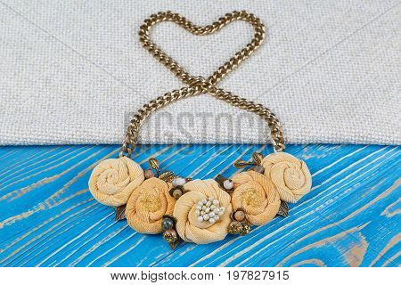Handwork necklace of on a golden chain laid out in the shape of a heart is lies on a blue wooden background