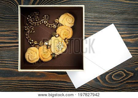 Peach-colored handmade necklace putted in a box and a letter of congratulations are lying on wooden background
