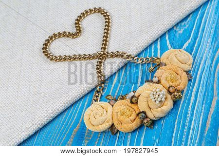 Handwork necklace of on a golden chain laid out in the shape of a heart is lies on a cloth background