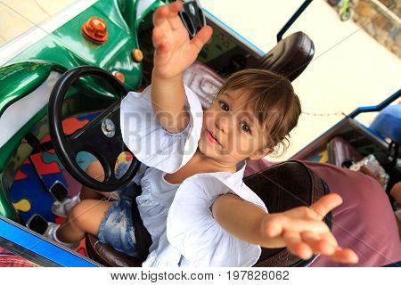 Little girl pulls her arms up while sitting on the driver's seat of a children's car