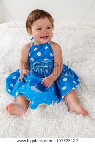 Little girl in a blue dress is sitting on the bed and laughs playing with a toy