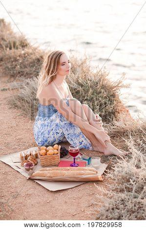 Blonde beautiful girl 22-24 year old having picnic with fresh bread fruits cakes and lemonade outdoors. Looking awat ar sea. Good morning. Summer season. 20s.