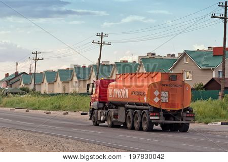 Truck Lukoil Hauling A Fuel Tanker Past A Country Cottage Settlement