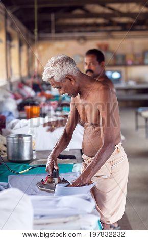 COCHIN, INDIA - JANUARY 21, 2016: Indian man working hard on Dhobi Ghat in Fort Cochin, Kerala