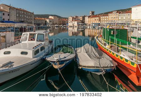 Boats and colorful houses reflected in the water of the old harbour in Cres