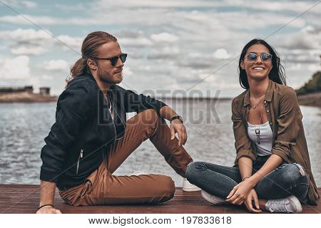 She means everything to him. Beautiful young couple sitting on the wooden platform near the lake while spending time outdoors