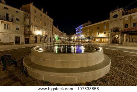 Fountain with reflection of lamps in the city of cres