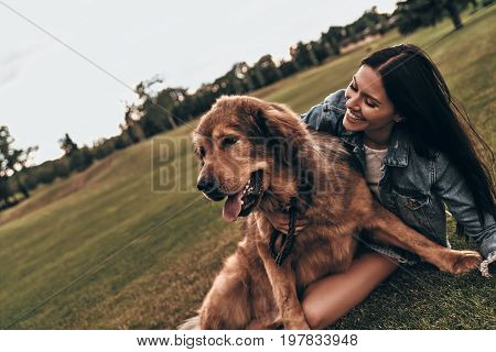 Moments of joy. Beautiful young woman keeping eyes closed and smiling while playing with her dog outdoors